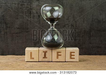 Living Time For Human Life Countdown, Lifetime Or Retirement Concept, Sandglass Or Hourglass On Wood