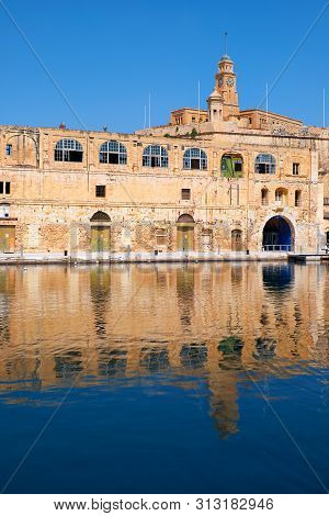 The Old Dock Buildings At Bormla (cospicua) Waterfront With The Fort St. Michael Clock Tower On The