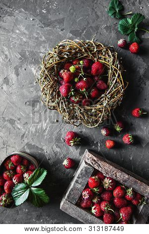 Delicious Strawberries With Yellow Flowers On A Dark Gray Background In A Vintage Wreath. Healthy Fo