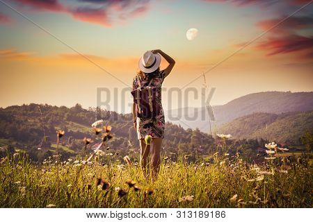 Traveler Woman In Meadow In Sunset. Young Woman Traveler Walking In Meadow. Traveler With Backpack I