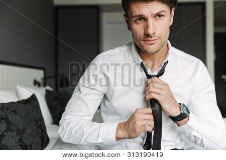 Image closeup of unshaved young man wearing formal suit unleashing his tie while sitting on bed in hotel room during business trip
