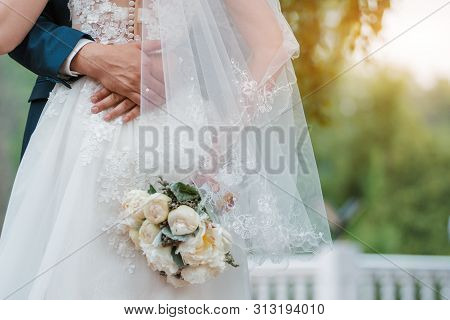 Newly Married Couple. Wedding Day. Bouquet Of The Bride In The Hands, The Grooms Embrace. Free Space