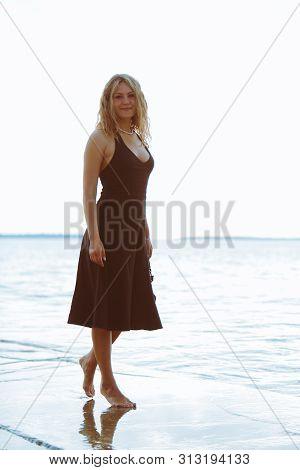 woman in black light dress walking barefoot by sea beach warm summer evening poster