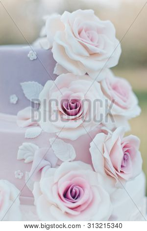 Close-up Of Parts Of A Three Tiered Wedding Cake In Pastel Colors Decorated With Realistic Pink Rose