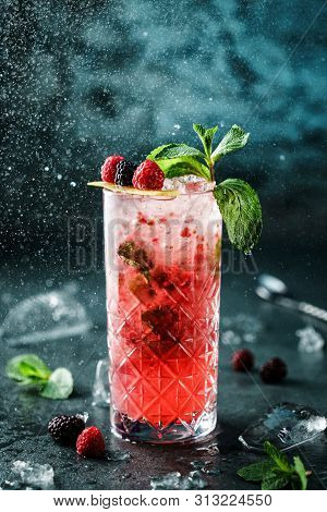 Fresh Berries Cocktail With Raspberry, Mint And Ice In Jar Glass On Dark Blue Background. Studio Sho