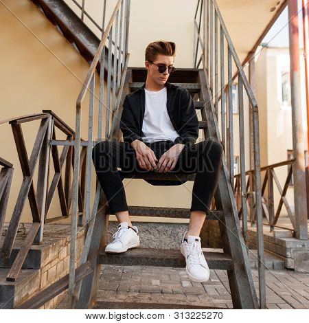 Stylish Young Hipster Man In Trendy Sunglasses In A Black Shirt In A T-shirt In Elegant Striped Pant