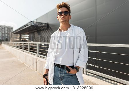 American Young Handsome Man Fashion Model In White Stylish Shirt In Blue Vintage Jeans In Trendy Sun