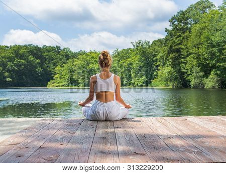 Attractive Woman Is Practicing Yoga And Meditation Sitting In Lotus Pose Near Lake. Young Woman Is M