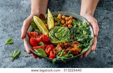 Hands Holding Healthy Superbowl Or Buddha Bowl With Salad, Baked Sweet Potatoes, Chickpeas, Broccoli