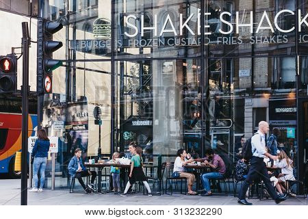 London, Uk - July 15, 2019: People Sitting At The Outdoor Tables Of Shake Shack In Victoria Station.