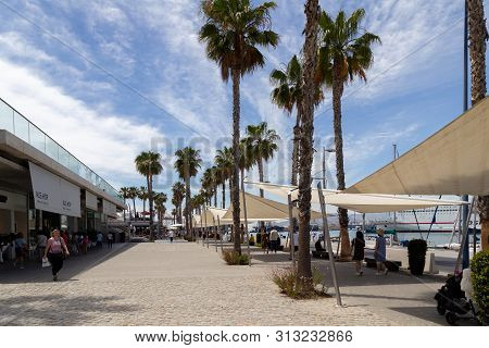 Malaga, Spain - May 24, 2019: People At The Paseo Del Muelle Uno, A Modern Beachfront Shopping And L