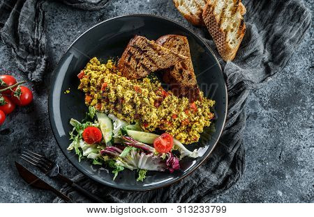 Vegan Tofu Scramble With Vegetables, Salad And Toasted Bread In Plate Over Grey Background. Healthy