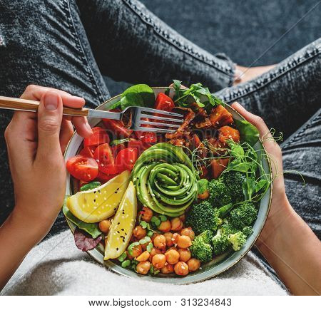 Woman In Jeans Holding Buddha Bowl With Salad, Baked Sweet Potatoes, Chickpeas, Broccoli, Greens, Av