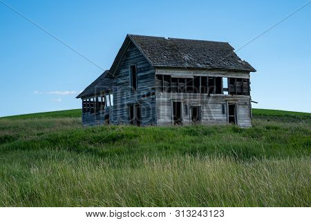 Spooky, Old Abandoned Farm House In The Rolling Hills Of The Palouse In Washington State. Windmills