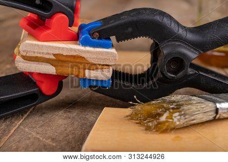 Gluing wood with waterproof adhesive. Pieces of wood pressed together with carpentry clamps. Place - carpentry workshop. poster