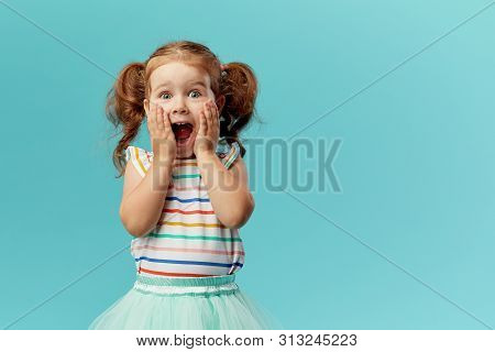 Portrait Of Surprised Cute Little Toddler Girl Child Standing Isolated Over Blue Background. Looking