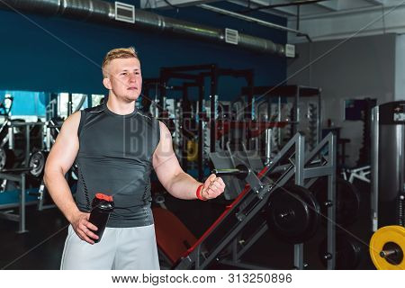Athlete Cheers Someone Off-screen In The Gym, Holding A Shaker Botle For Sports Nutrition In His Han