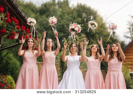 Happy Bride With Bridesmaid Hold Bouquets And Have Fun Outside. Beautiful Bridesmaid In Same Dresses