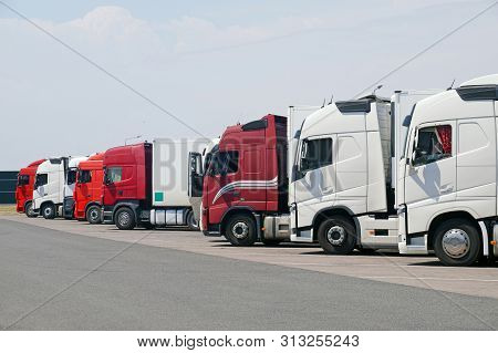 Resting Place. Various Types Of Trucks In The Parking Lot Next To The Motorway.