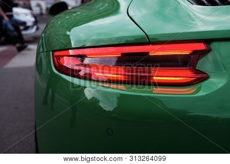 Green sports car. Car backlight on before the crosswalk. Closeup of a modern red LED light. Unexpected stop. Back of a luxury car. poster