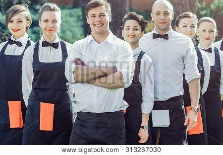 Large Group Of Waiters And Waitresses Who Stand In The Row Behin