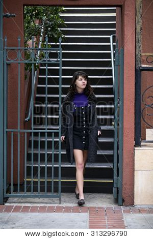 Young Female College Student Going Down The Stairs From A Rented Apartment Or Condo Dorm Into The St