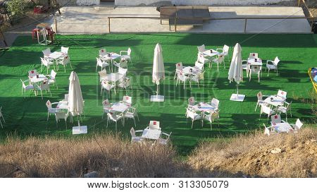 Alora, Spain - July 10, 2019: Artificial Patio Grass Area With White Chairs, Tables And Parasols In