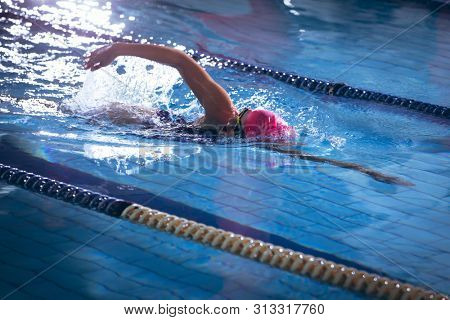 Side view of an African-American woman wearing a pink swimming cap and goggles doing a freestyle stroke in a swimming pool