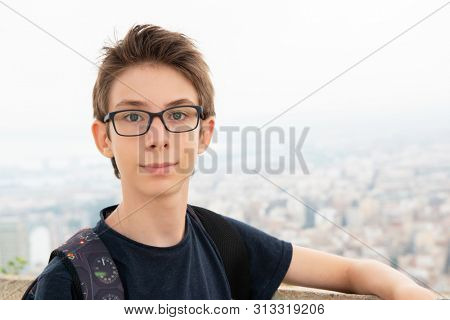 Handsome young boy wearing glasses posing over background of panorama of Alicante (Spain). City view from Mount Santa Barbara with teen foreground