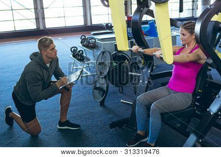 Side view of handsome young Caucasian male trainer assisting pretty young Caucasian  female athlete with exercise in fitness studio. Bright modern gym with fit healthy people working out and training