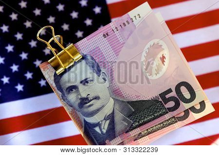 Some New Zealand Dollars With The American Flag In The Background.