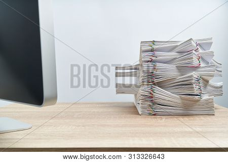 Arrange Of Overload Paperwork Report And Computer On Wooden Table