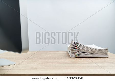 Pile Of Document Report And Computer On Wooden Table