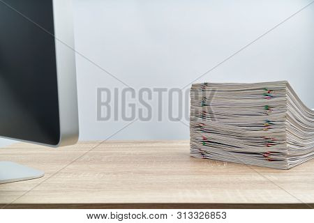 Stack Of Paperwork Overload Report And Computer On Wooden Table