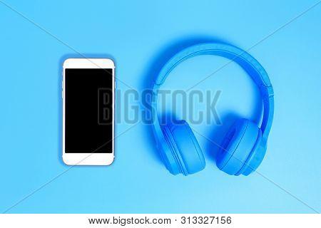 Blue Headphones, Top View Of Headphones On Blue Background. Minimalist Photo Of Earphones With Copy