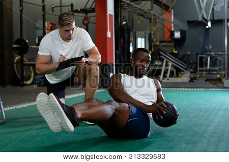 Front view of handsome young Caucasian male trainer writing on clipboard while young fit African-american male athletic exercising with exercise ball in fitness center. Bright modern gym with fit