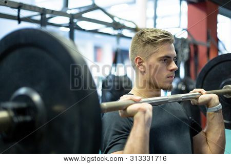 Close-up of handsome young fit Caucasian male athletic exercising with barbell in fitness center. Bright modern gym with fit healthy people working out and training