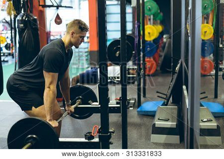 Side view of handsome fit young Caucasian male athletic exercising with barbell in fitness center. Bright modern gym with fit healthy people working out and training
