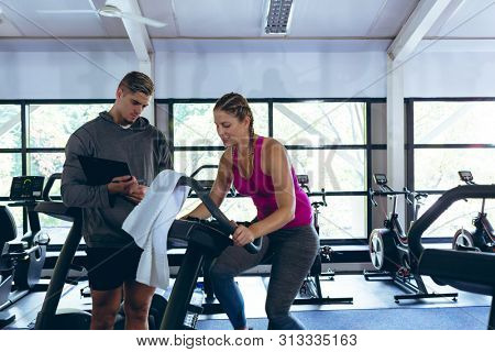 Front view of handsome Caucasian male trainer assisting pretty Caucasian female athletic to work out on exercise bike in fitness center. Bright modern gym with fit healthy people working out and