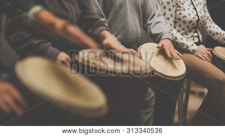Group of people playing on drums - therapy by music
