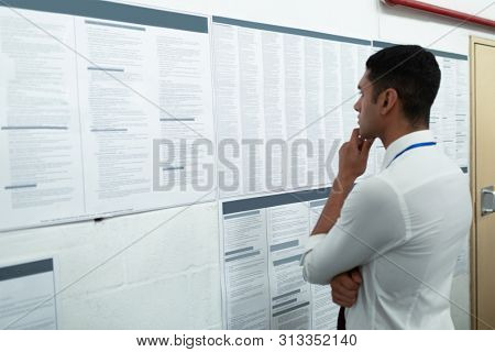 Side view of handsome young mixed-race male supervisor looking at inventory records on wall. This is a freight transportation and distribution warehouse. Industrial and industrial workers concept poster