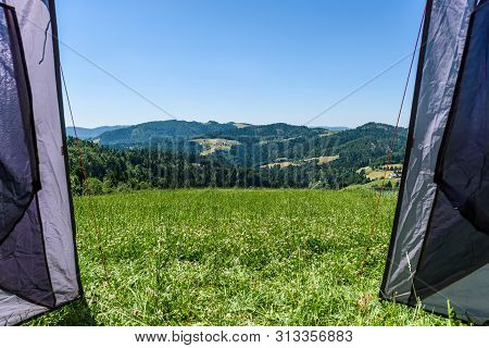 Camping Tourist Tent Set Up On Meadow In The Mountains. Small Tent In Green Mountains Of Slovenia.