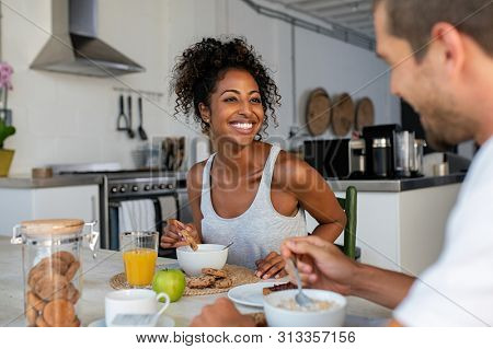 Happy african woman in conversation with man while enjoying morning breakfast. Smiling multiethnic couple eating healthy cereals and milk with cookies and orange juice.