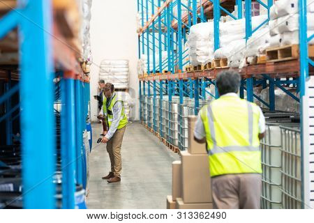 Rear view of mature Asian male worker pulling pallet jack with cardboard boxes while diverse supervisors work in the aisle in warehouse. This is a freight transportation and distribution warehouse.