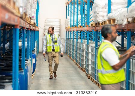 Front view of Caucasian male supervisor walking in aisle in warehouse. In front of him an Asian staff member is writing on clipboard. This is a freight transportation and distribution warehouse.