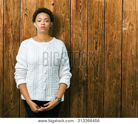 Beautiful young african american woman wearing sweater over isolated background Relaxed with serious expression on face. Simple and natural looking at the camera.