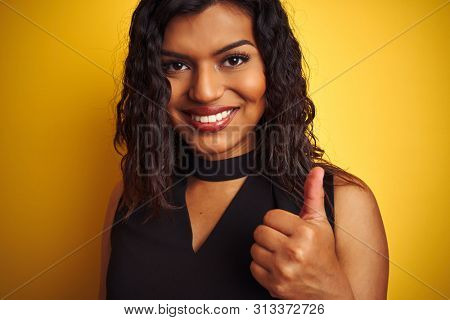 Transsexual transgender woman wearing black t-shirt over isolated yellow background happy with big smile doing ok sign, thumb up with fingers, excellent sign