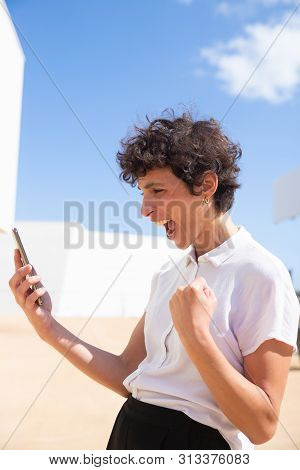 Excited Woman Holding Cell Phone Outdoor. Emotional Middle Aged Businesswoman Using Smartphone Benar