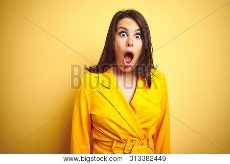 Young beautiful brunette woman wearing elegant dress over yellow isolated background afraid and shocked with surprise expression, fear and excited face.