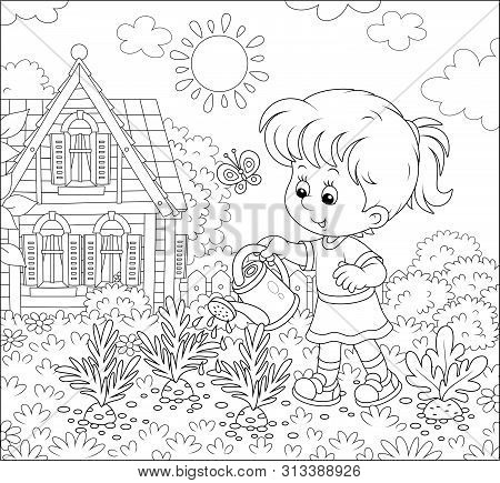 Smiling Little Girl Watering Carrots In Her Small Kitchen Garden In Front Of A House On A Sunny Summ